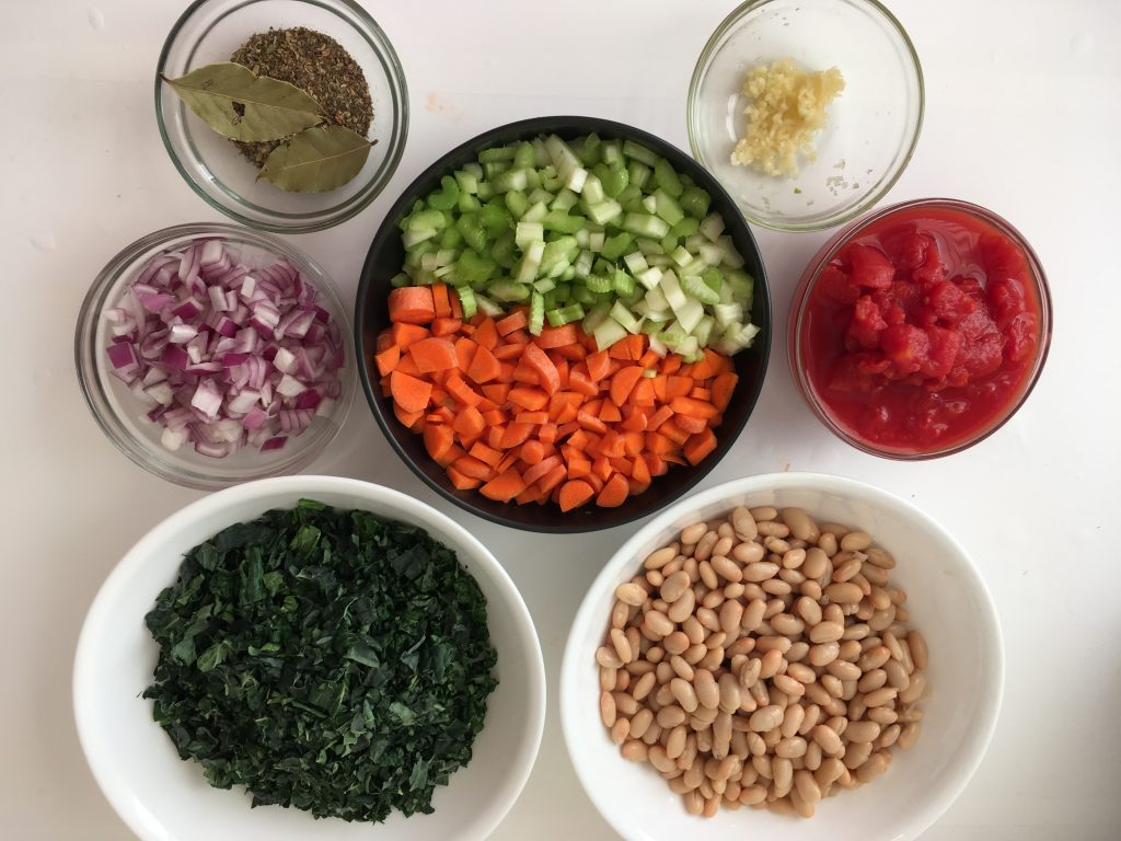 Bowls of ingredients for Kale Bean Soup: spices and bay leaf,