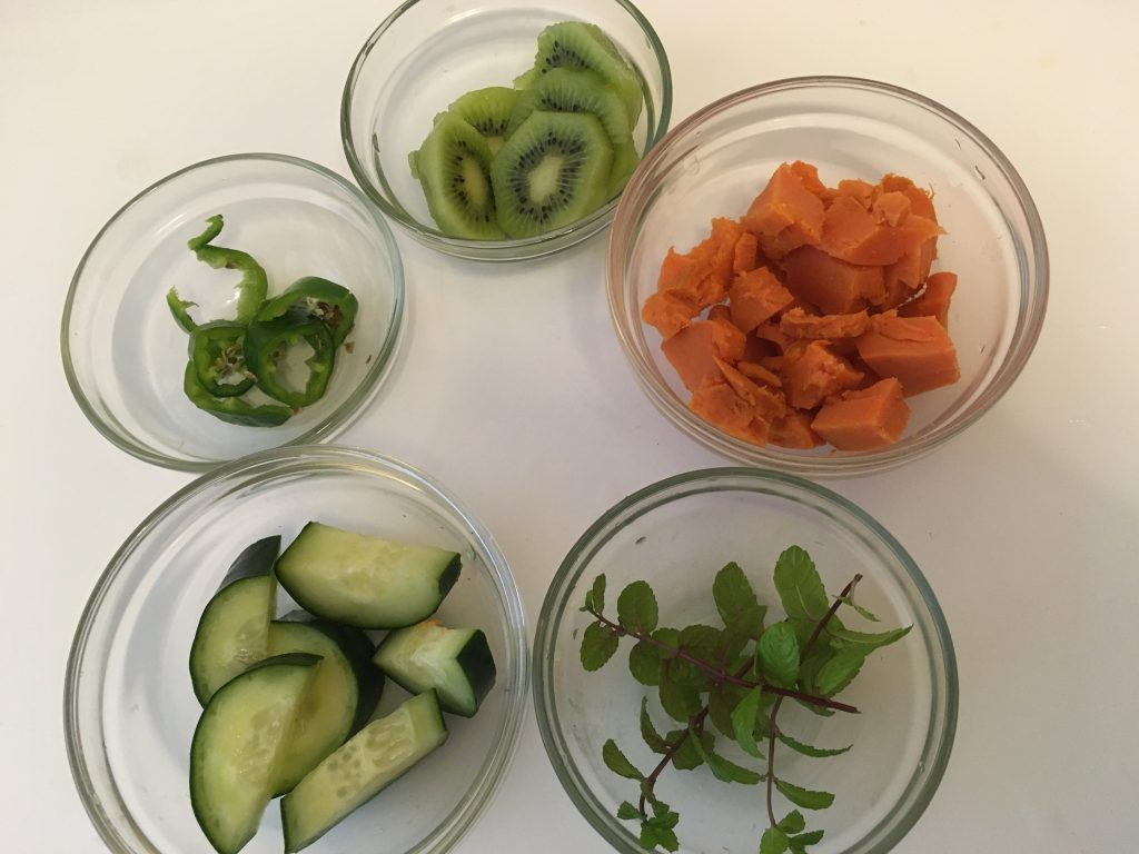 Five bowls with smoothie extras: jalapeno slices, kiwi slices, cubed sweet potato, mint sprigs and cucumbers